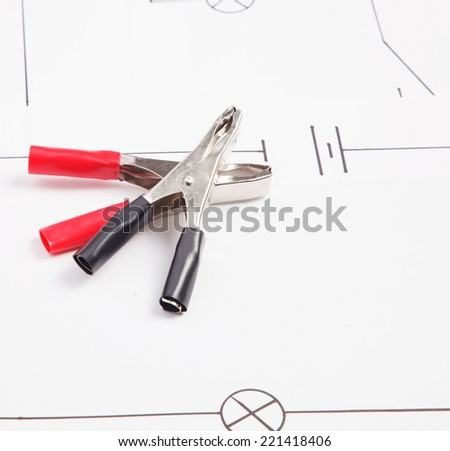 Electric clamps on a background of the electric scheme  - stock photo