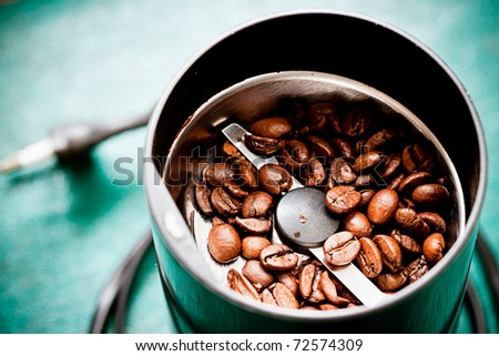 Electric coffee-mill machine with roasted coffee beans on the kitchen table with green tabletop - stock photo