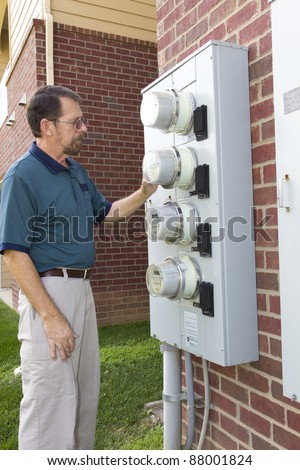 Electric company technician checking meter after customer complained of high electric bills
