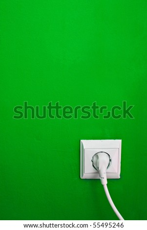 electric consumption - electric outlet on green wall - stock photo
