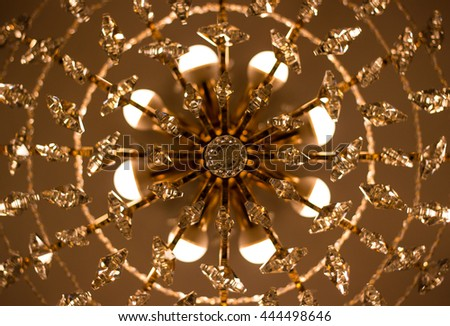 electric crystal ceiling chandelier with beautiful ornaments - stock photo