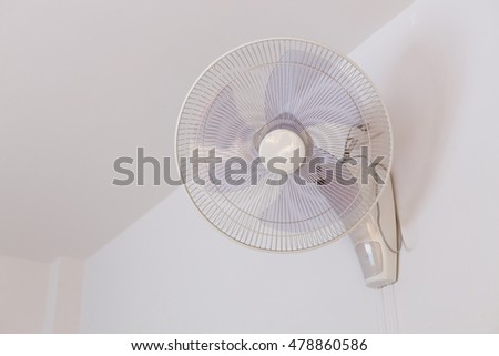 electric fan hanging on white mortar wall