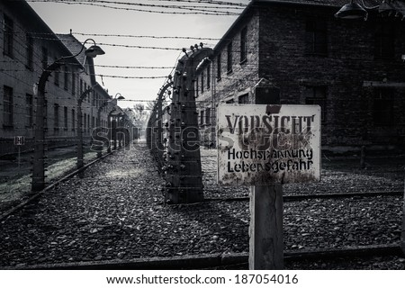 Electric fence and warning sign in former Nazi concentration camp Auschwitz I, Poland - stock photo