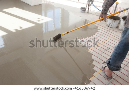 Electric floor heating system installation in new house.Worker use a  Roller for pouring concrete floor