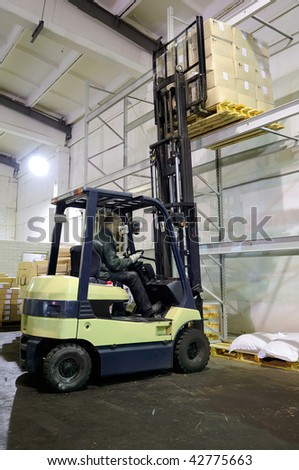 Electric forklift in warehouse loading cardboard boxes - stock photo