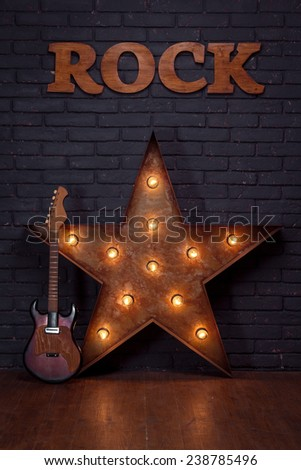 Electric Guitar And Iron Star Leaning On Brick Wall - stock photo