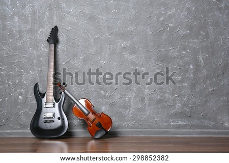 Electric guitar and violin on gray wall background - stock photo