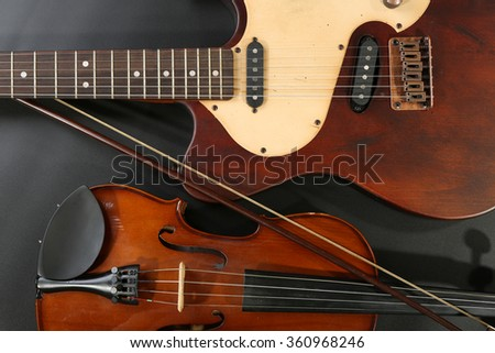 Electric guitar and violin on grey background