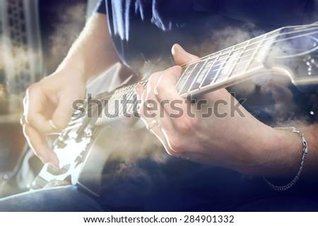 Electric guitar in male hands in closeup - stock photo