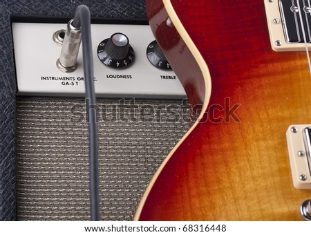 Electric guitar leaning against vintage amplifier with patch cord - stock photo