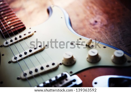 Electric guitar  on a grungy old wooden surface with impressional feeling. - stock photo