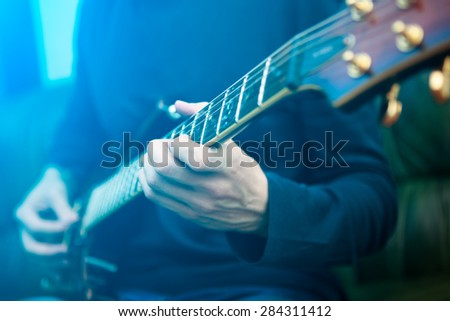 Electric guitar player. Blue lensflare - stock photo