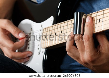 Electric guitar player performing song with slider - stock photo