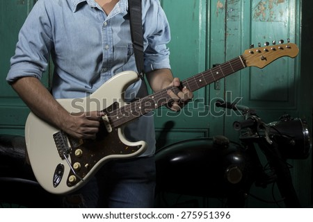 Electric guitar player, playing with old vintage motorcycle background with wooden old door - stock photo