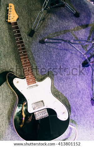 Electric guitar top view in sound recording studio. Electric guitar flat lay on sound recording studio floor. Musical instrument  closeup with free space. - stock photo