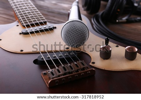 Electric guitar with microphone on wooden table close up - stock photo