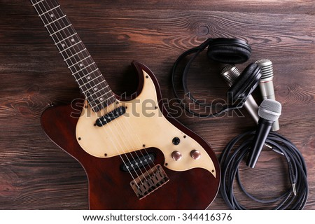 Electric guitar with microphones and headphones on wooden table close up - stock photo