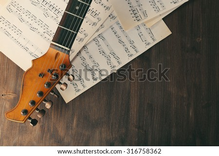 Electric guitar with music notes on wooden table close up - stock photo