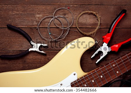Electric guitar with pliers and cords on wooden background - stock photo