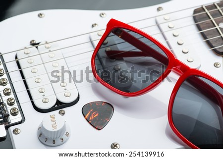 Electric guitar with red sunglasses and mediator - stock photo