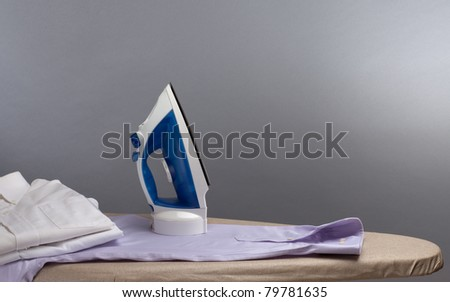 Electric iron on an ironing board, with three men's dress shirts. Photographed with studio lighting in front of a gray backdrop. Composition leaves room for copy space. - stock photo