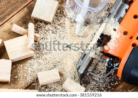 Electric jigsaw with many wooden bricks full of sawdust. On old scratched wooden table, work tools concept.