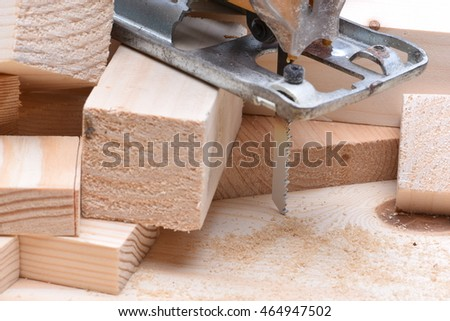 Electric jigsaw with wooden bricks closeup