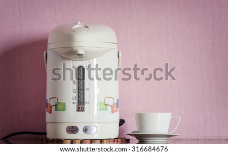 Electric kettle and cup on table,design with vintage style. - stock photo