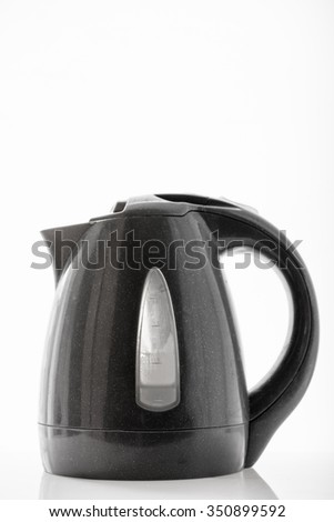 Electric kettle on a dark colored window with light from the window. - stock photo