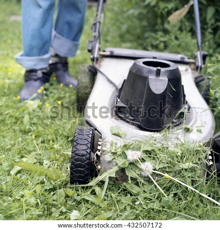 Electric lawn mower in the foreground and human legs in the blurred background, selective focus outdoor shot