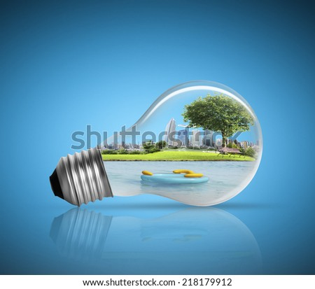 Electric light bulb and  green energy city - stock photo