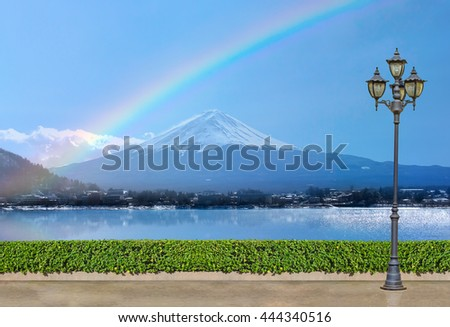 electric light lamp post at green bush fence on concrete floor at Fuji mountain Kawaguchi lake with rainbow on blue sky background, exterior park and outdoor concept - stock photo