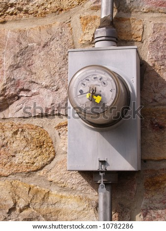 electric meter by a stone wall - stock photo