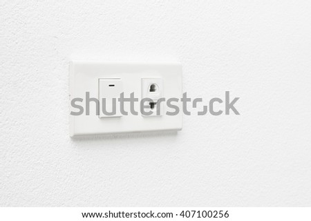 Electric outlet and switch on white wall - stock photo