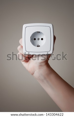 Electric outlet in a hand - stock photo