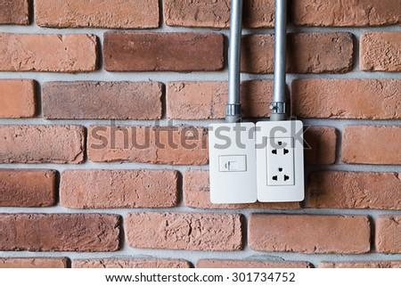 Electric outlet on brick wall texture - stock photo