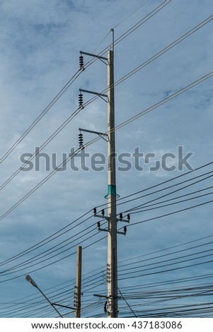 Electric pole and electricity line with against blue cloudy sky, abstract background. - stock photo