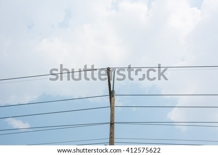 Electric pole with blue sky and white clouds - stock photo