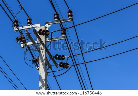 Electric Pole with Power Lines against Bright Blue Sky. - stock photo