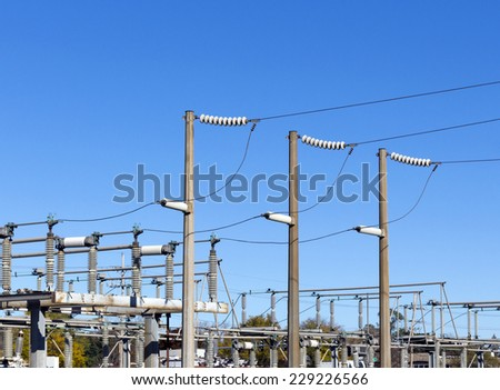 Electric poles in blue sky background. Part of power plant. - stock photo