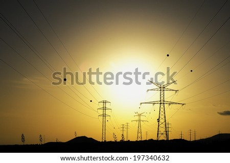 Electric Power Line Pylon over a colored Sunset - stock photo