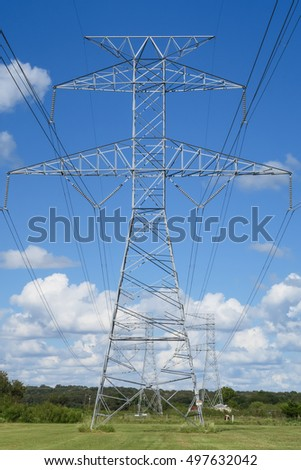 electric power line towers seen straight on in front of trees and clouds