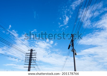Electric power lines and pylon against blue sky