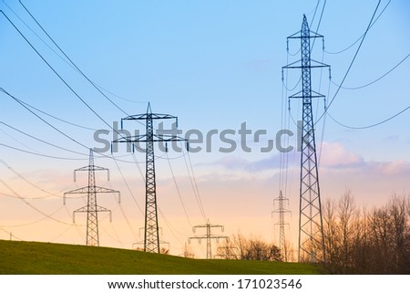Electric power lines and pylons at sunset - stock photo