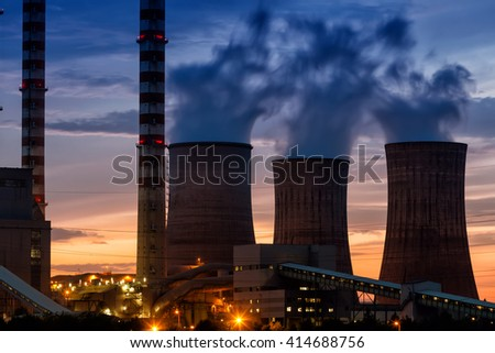 Electric power plant at dusk with orange sky in Kozani Greece - stock photo