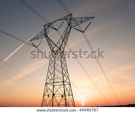 Electric power pylon and wires silhouetted by ab colorful sunset. - stock photo
