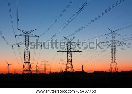 Electric power pylons at twilight. At the horizon wind turbines. - stock photo