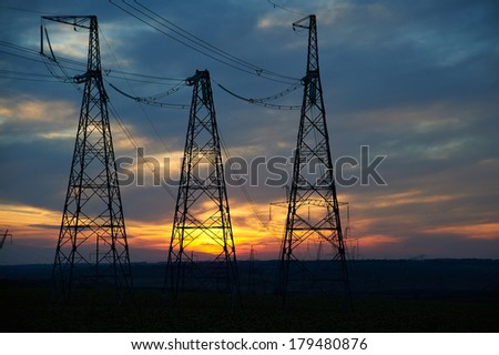 Electric powerlines over sunrise or sunset - stock photo