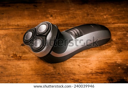 Electric rotary shaver on wooden board - stock photo