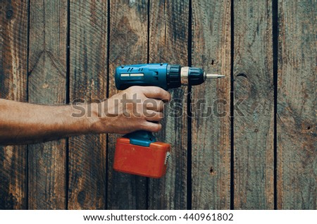 Electric screwdriver in hand at wooden desk background - stock photo